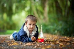 有小船的小男孩,说谎在地面上在公园 免版税库存图片