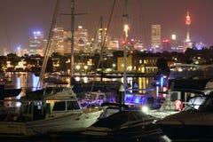 有小船的悉尼港口和地平线在晚上 库存图片