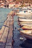有小船的木码头在港口,特罗吉尔,克罗地亚,红色过滤器 免版税库存照片
