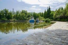 有小船的湖边道路和人行桥在晴朗的s的背景中 库存图片