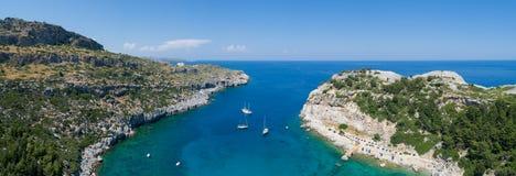 有小船的美好的海滩全景在罗得岛海岛上在希腊 绿松石水和天空蔚蓝 库存图片