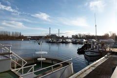 有小船的船坞在一条河,在蓝色多云天空下,在一个冬天早晨,与产业大厦 库存图片