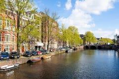 有小船的阿姆斯特丹运河沿河的河岸在春天 荷兰 库存图片