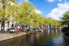 有小船的阿姆斯特丹运河沿河的河岸在春天 荷兰 免版税库存照片
