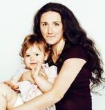有小逗人喜爱的女儿的年轻母亲白色的,愉快的微笑的家庭里面隔绝了可爱,生活方式现代人民 免版税库存照片