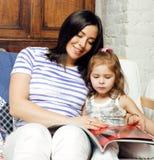有小逗人喜爱的女儿的年轻母亲白色的,愉快的微笑的家庭里面隔绝了可爱,生活方式现代人民 免版税图库摄影