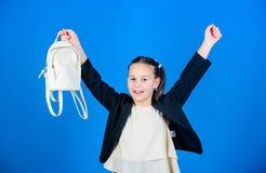 有小逗人喜爱的背包的女小学生正式样式衣裳 不要忘记您的背包 怎么学会适合的背包恰当地 库存图片