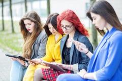 有小配件的四个女孩坐长凳 互联网、人脉、研究和生活方式的概念 免版税库存图片