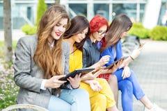 有小配件的四美女坐长凳 互联网、人脉、研究和生活方式的概念 库存照片