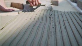 有小铲和灰浆的工作者 在他的膝盖的建造者铺平与一把手工小铲的水泥灰浆在 影视素材