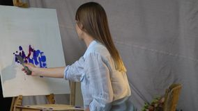 有小铲的深色的画家排列在帆布的蓝色和红色油漆 股票录像