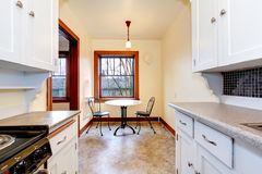 有小餐桌的白色老厨房。 免版税库存图片