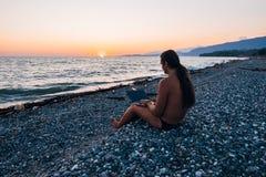 有小马传说的年轻人与在晚上日落海海滩的笔记本一起使用 免版税库存照片