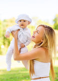 有小婴孩的愉快的母亲坐毯子 库存照片