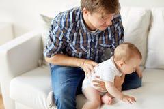 有小婴孩的愉快的年轻父亲在家 库存图片