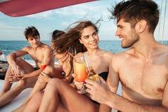 有小组的朋友喝和在帆船的党 库存照片