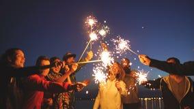 有小组年轻的朋友海滩党 跳舞和庆祝与在暮色日落的闪烁发光物的朋友 股票录像