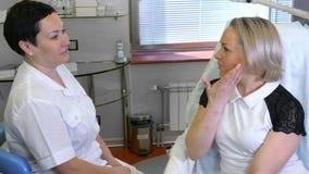有少妇客户的女性美容师坐和谈话在美容师办公室 免版税库存图片
