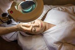 有少妇患者的美容师诊所的,顶视图 面部皮肤回复的剥的和洗涤的做法,关闭  库存图片