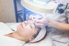 有少妇患者的美容师诊所的 面部皮肤回复的剥的和洗涤的做法 免版税库存照片