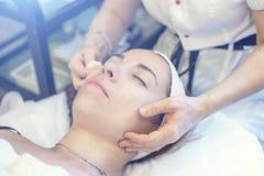 有少妇患者的美容师诊所的 面部皮肤回复的剥的和洗涤的做法 库存图片