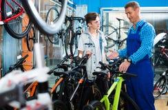 有少年男孩顾客的卖主在自行车商店 免版税库存照片