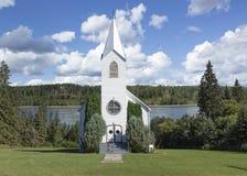 有尖顶的白色国家教会与流动在背景的河 免版税库存图片