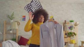 有尝试在一个镜子前面的衣裳的一种非洲的发型的画象非洲妇女在他的现代公寓缓慢的mo 股票录像