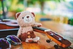 有尤克里里琴和太阳镜的微笑的玩具熊玩偶 库存图片
