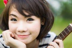 有尤克里里琴的亚裔美丽的妇女在庭院里 免版税库存图片