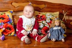 有尾巴的小婴孩坐有被绣的枕头和玩具的一个沙发 库存照片
