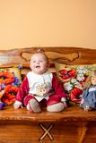 有尾巴的小婴孩坐有被绣的枕头和玩具的一个沙发 免版税库存照片