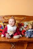 有尾巴的小婴孩坐有被绣的枕头和玩具的一个沙发 免版税库存图片