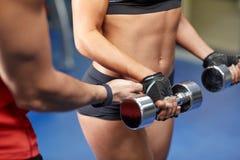 有屈曲在健身房的哑铃的妇女肌肉 免版税库存照片
