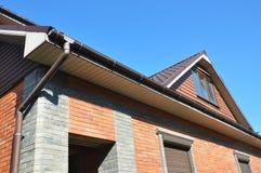 有屋顶窗口的顶楼,新的安装的雨天沟和水落管用管道输送 库存图片