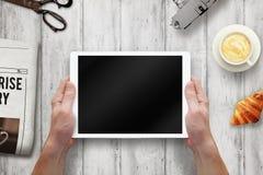 有屏幕的片剂在人手上 与报纸,新月形面包,在桌上的咖啡的早晨时间 库存图片