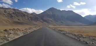 有山和天空的一条开放路在背景中 免版税图库摄影