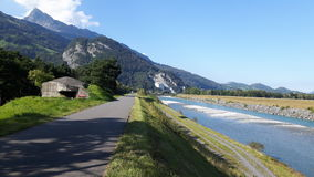 有山和蓝天的莱茵河和自行车道路在背景 免版税库存图片
