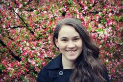 有山楂子开花的青少年的女孩 图库摄影