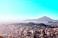 有山的城市与海和蓝天 免版税库存图片