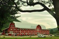有山的大红色谷仓 库存照片