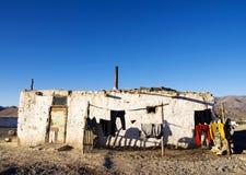 有山脉的老被风化的房子在背景中 免版税库存照片