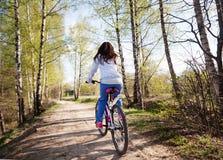 有山自行车的美丽的少妇在春天森林里 免版税库存图片