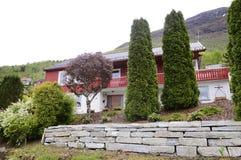 有岩石前面庭院的大红色议院 免版税库存照片