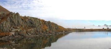有岩石反射的湖在Grimsel通行证顶部在瑞士 免版税库存图片