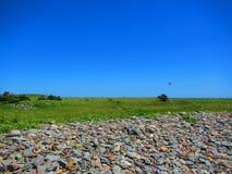 有岩石堆的海边在距离的草甸和kiteboarder 库存图片