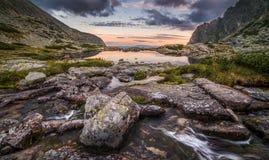 有岩石的Mountain湖在日落的前景 免版税库存照片