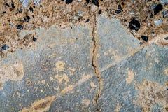 有岩石纹理的破裂的水泥墙壁 库存图片