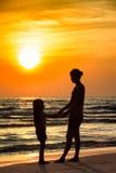 有岸上女儿的剪影母亲 免版税库存照片