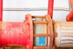 有工业修造的尘土肮脏的里面的联合管道系统老大配管红色 库存图片